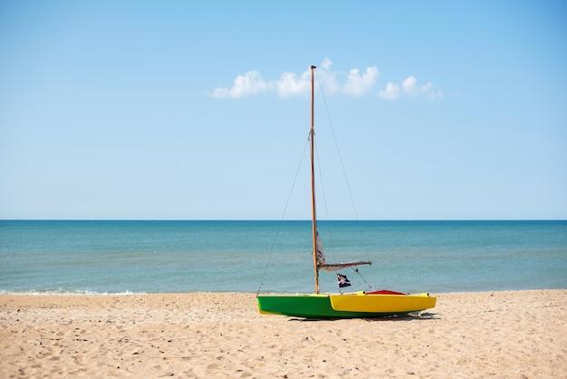 海岸には帆と小さな海賊旗が付いたボートがありますボートの上空と小さな雲