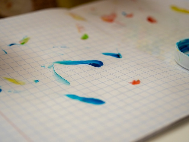 На листе тетради мазки разноцветной краски нарисованные ребенком. выборочный фокус.