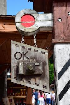 路上、木製の看板、店やスタジオの広告として木から彫られた様式化されたデジタルカメラ