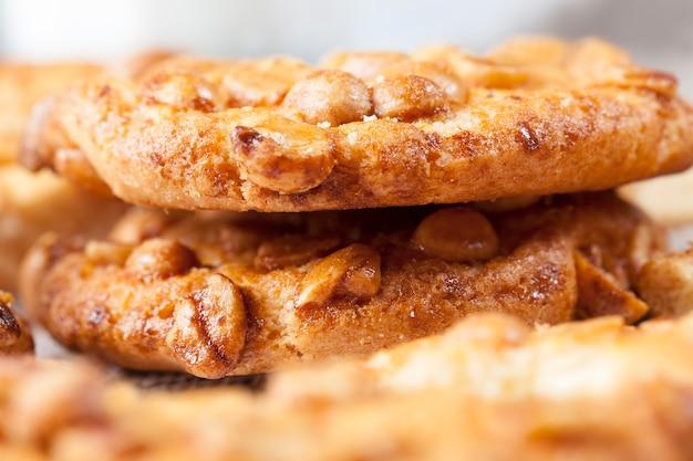 ピーナッツ入りの丸いクッキーキャラメルの表面に、小麦粉とローストピーナッツから作られた新鮮なカリカリのクッキー、さまざまな材料からのおいしいクッキー