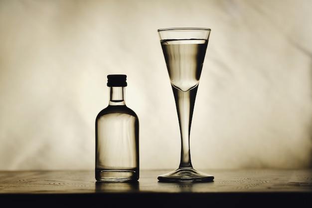 테이블에는 술 한 병과 아름다운 유리 잔이 있습니다.