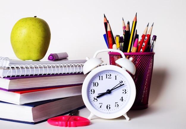 На столе стопка книг, канцелярские товары, белый будильник и яблоко.