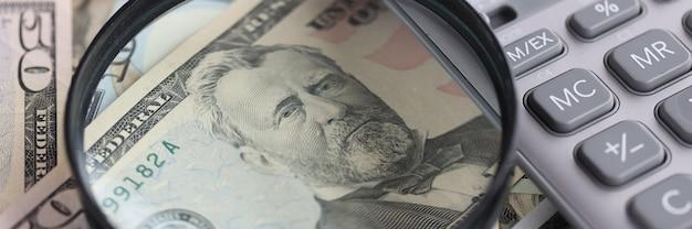 На столе - увеличительное стекло и калькулятор американских банкнот. поиск концепции финансовых решений