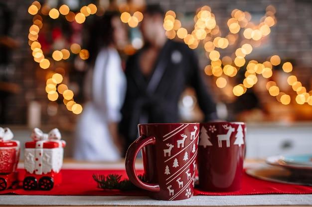На столе красивые кружки с какао. кухня украшена на рождество и новый год, люди в халатах обнимают друг друга.