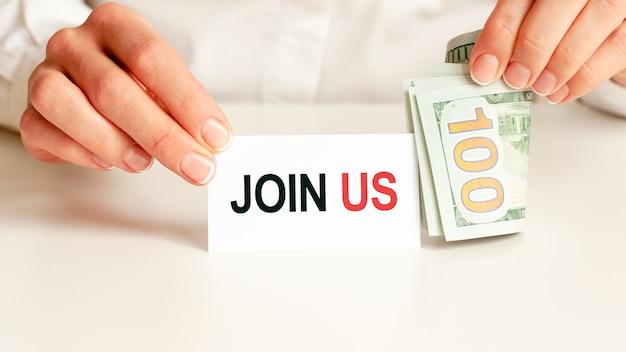 テーブルの上には、請求書、ドルの束、そしてそれが書かれているサインがあります-私たちに参加してください。金融と経済学の概念。