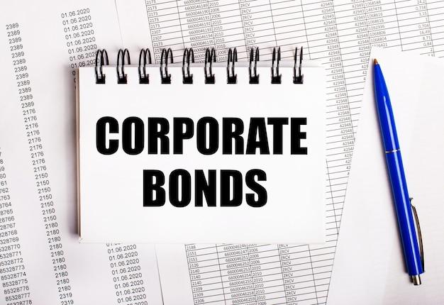 На столе находятся графики и отчеты, на которых лежат синяя ручка и блокнот с надписью corporate bonds.