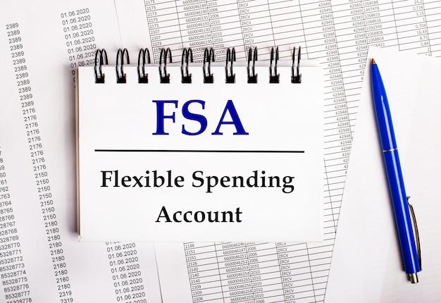 На столе находятся диаграммы и отчеты, на которых лежат синяя ручка и блокнот со словом fsa flexible spending account.