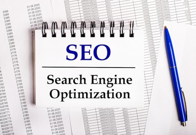 На столе находятся диаграммы и отчеты, на которых лежат синяя ручка и блокнот со словом seo search engine optimization.