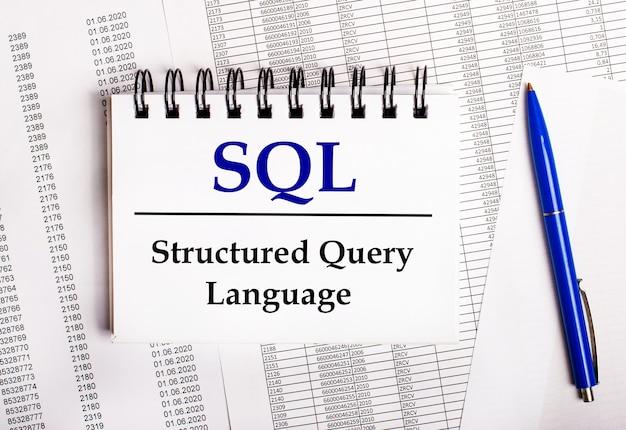 На столе находятся диаграммы и отчеты, на которых лежат синяя ручка и записная книжка со словом sql structured query language.