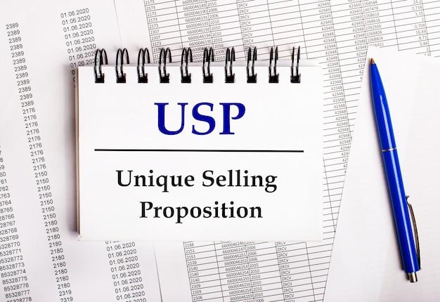 テーブルの上にはチャートとレポートがあり、その上に青いペンとuspユニークセリングプロポジションという言葉が書かれたノートがあります。