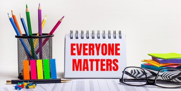테이블에는 스탠드에있는 색연필, 밝은 색의 스티커, 안경 및 everyone matters라는 문구가있는 노트북이 있습니다.