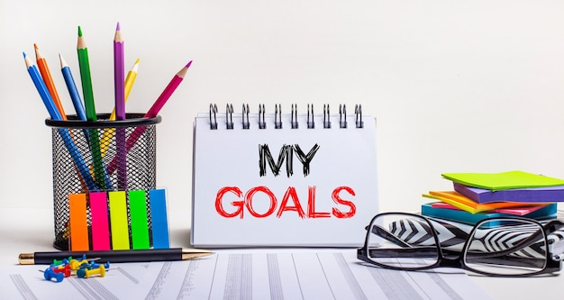 테이블에는 스탠드의 색연필, 밝은 색의 스티커, 안경 및 my goals라는 문구가있는 노트북이 있습니다. 동기 부여 개념. 행동을 요구하다