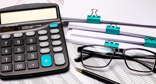 テーブルの上には、書類、電卓、レポート、ペン、黒いフレームのメガネがあります