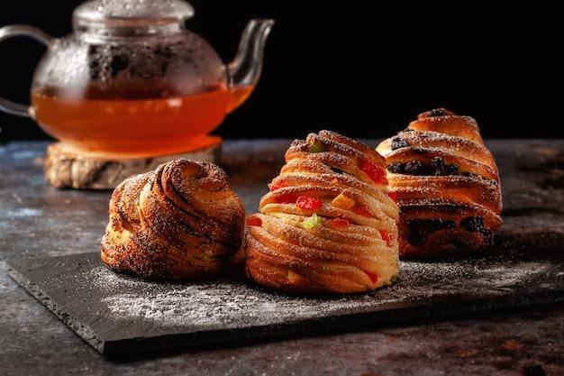 テーブルの上には、レーズン、砂糖漬けの果物、ケシの実が入ったクラフィンに粉砂糖が振りかけられています。