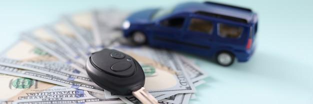 На столе лежат деньги автомобиль и ключи от концепции покупки автомобиля по выгодной цене.