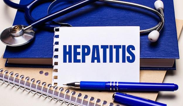 テーブルの上には、メモ帳、聴診器、ペン、そして肝炎のテキストが書かれた一枚の紙があります。医療コンセプト