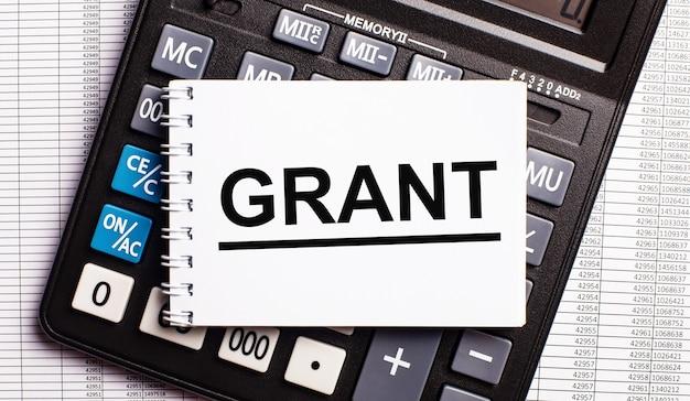 На столе находятся отчеты, калькулятор и карточка со словом grant. бизнес-концепция