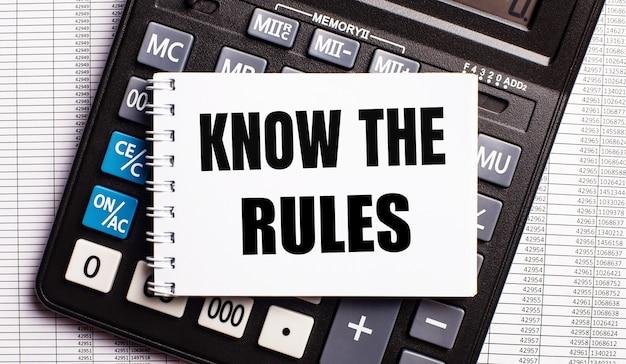 テーブルの上には、レポート、計算機、そして「ルールを知っている」という言葉が書かれたカードがあります。ビジネスコンセプト Premium写真