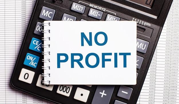 На столе отчеты, калькулятор и карточка с надписью нет прибыли.