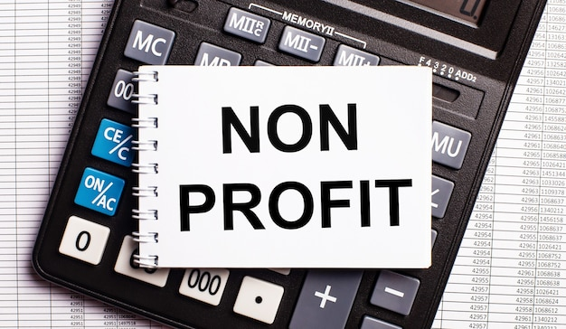 На столе находятся отчеты, калькулятор и карточка с надписью non profit. бизнес-концепция