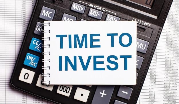 테이블에는 보고서, 계산기 및 투자 할 시간이라는 단어가 적힌 카드가 있습니다. 비즈니스 개념