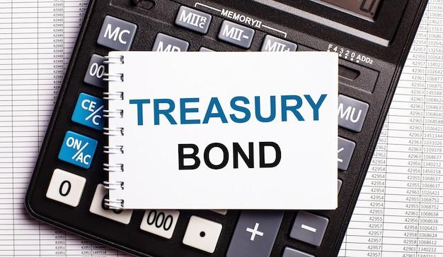 На столе находятся отчеты, калькулятор и карточка с надписью treasury bond.