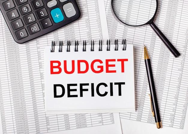 На столе отчеты, увеличительное стекло, калькулятор, ручка и белый блокнот с текстом дефицит бюджета. бизнес-концепция