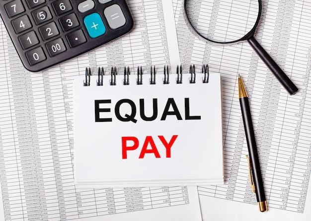 На столе отчеты, увеличительное стекло, калькулятор, ручка и белый блокнот с надписью equal pay. бизнес-концепция
