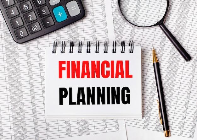 На столе отчеты, увеличительное стекло, калькулятор, ручка и белый блокнот с текстом финансовое планирование. бизнес-концепция