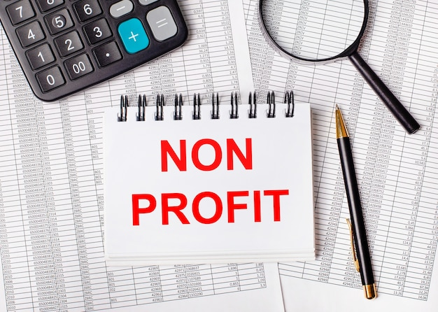 На столе отчеты, увеличительное стекло, калькулятор, ручка и белый блокнот с надписью non profit. бизнес-концепция