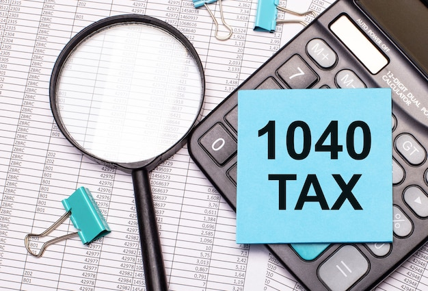На столе отчеты, увеличительное стекло, калькулятор и синяя наклейка с надписью 1040 tax. бизнес-концепция