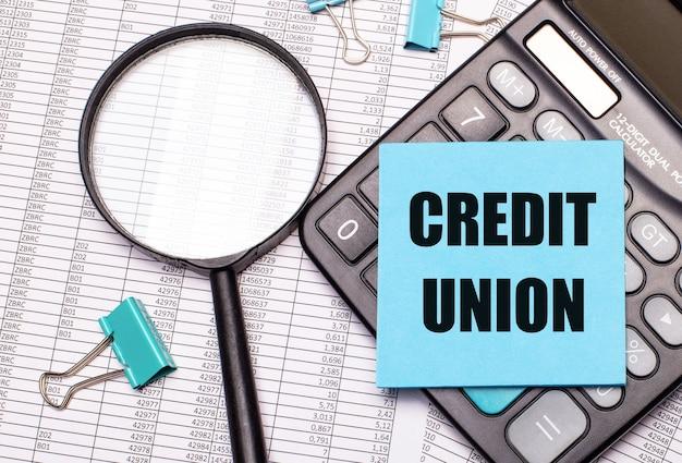На столе отчеты, увеличительное стекло, калькулятор и синяя наклейка с надписью credit union.