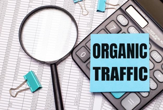 テーブルには、レポート、虫眼鏡、電卓、organictrafficという言葉が書かれた青いメモステッカーがあります。