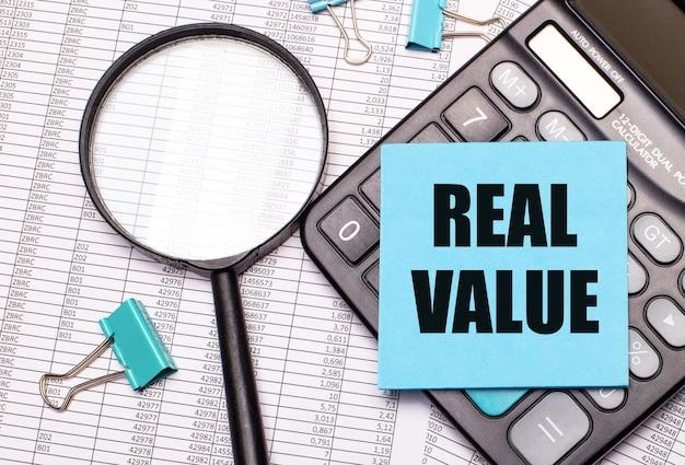 На столе отчеты, увеличительное стекло, калькулятор и синяя наклейка с надписью real value.