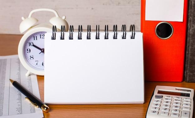 テーブルの上には、レポート、白い目覚まし時計、電卓、紙のフォルダー、ペン、テキストやイラストを挿入するスペースのある白いノートがあります。テンプレート。ビジネスコンセプト