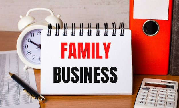 テーブルの上には、レポート、白い目覚まし時計、電卓、紙のフォルダー、ペン、familybusinessの白いノートがあります。ビジネスコンセプト