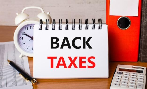 На столе отчеты, белый будильник, калькулятор, папки для бумаг, ручка и белый блокнот с текстом налоги назад. бизнес-концепция