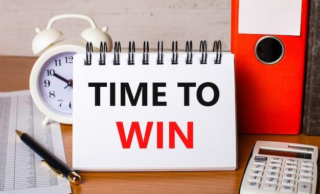 На столе отчеты, белый будильник, калькулятор, папки для бумаг, ручка и белый блокнот с текстом «время выиграть». бизнес-концепция