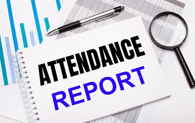 テーブルには、レポート、図、ペン、虫眼鏡、および出席レポートのテキストが記載された白いメモ帳があります。ビジネスコンセプト