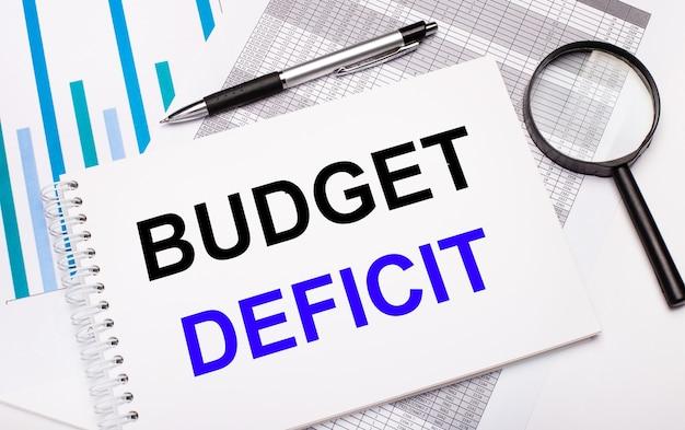 テーブルの上には、レポート、図、ペン、虫眼鏡、そして予算赤字のテキストが書かれた白いメモ帳があります。ビジネスコンセプト