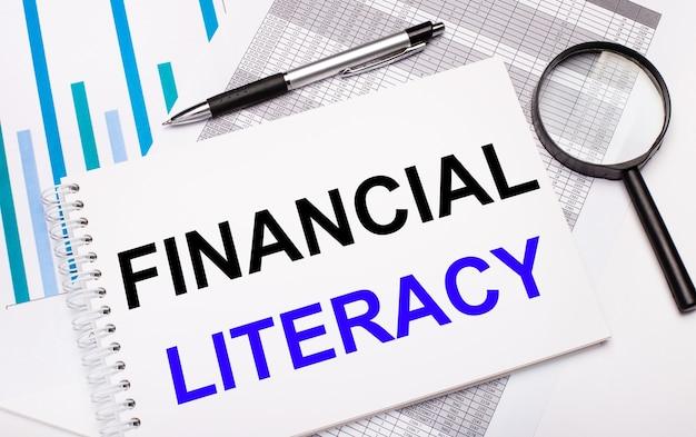 На столе находятся отчеты, диаграммы, ручка, увеличительное стекло и белый блокнот с текстом «финансовая грамотность». бизнес-концепция