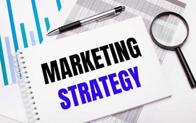 테이블에는 보고서, 다이어그램, 펜, 돋보기 및 마케팅 전략 텍스트가 있는 흰색 메모장이 있습니다. 비즈니스 개념