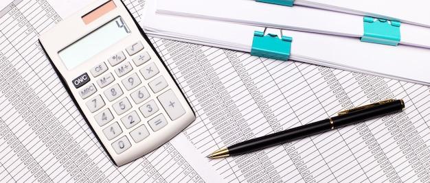 テーブルの上には、レポート、ドキュメント、ペン、白い電卓があります