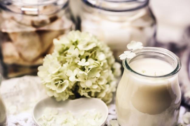 テーブルの上には白いろうそくと柔らかい花があります