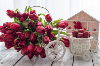 On the table in a basket there are a lot of red tulips and a basket with strawberries