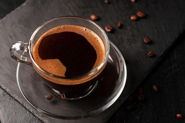 На столе чашка свежесваренного ароматного черного кофе.