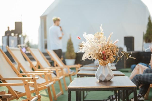 테이블에는 말린 꽃이 든 장식용 꽃병이 있습니다. 옥상에서 휴식을 취할 수 있는 아름다운 여름 장소