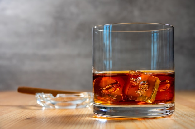 테이블에는 얼음 조각이 든 위스키 한 잔이 있습니다. 디 포커스 시가가 든 재떨이