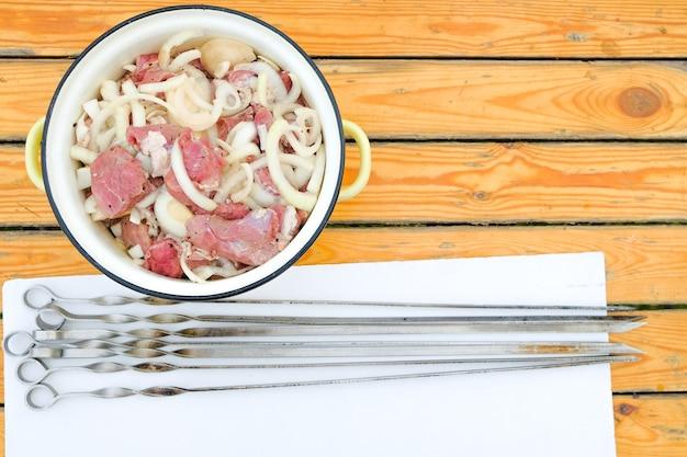 テーブルの上には、新鮮な赤い肉片と刻んだ玉ねぎが入った鍋があります