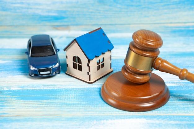 탁자 위에는 판사의 망치, 집, 차가 있습니다. 재산 소송 개념